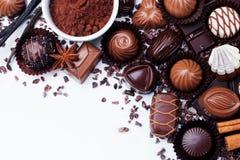 Asortyment czekoladowi cukierki, kakaowi produkty i pikantność na białym tle, Odgórny widok kosmos kopii obraz royalty free