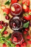 Asortyment d?emy, sezonowe jagody, wi?nia, mennica i owoc w szklanym s?oju, zdjęcie royalty free