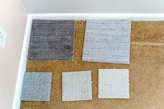 Asortyment dywan próbki rozkładać nad starym, brudnym dywanem w domu, przygotowywa decydować na nowej podłodze zdjęcia stock