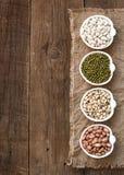 Asortyment legumes w pucharach na drewnianym stole Zdjęcia Stock