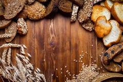 Asortyment piec chleb na drewnianym stołowym tle fotografia stock