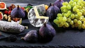 Asortyment przekąski z owoc i winogronem na starym drewnianym stole serowymi i kiełbasianymi Odg?rny widok kosmos kopii zdjęcia stock