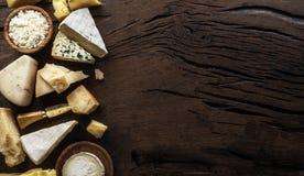 Asortyment różni serowi typy na drewnianym tle Odgórny widok zdjęcia stock