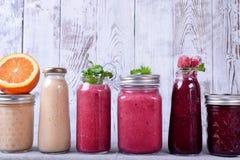 Asortyment różni smoothies nakrywający z owoc, jagodami i mennicą na stole, zdjęcie royalty free