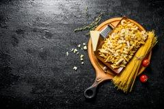 Asortyment r??ni typy surowa pasta na tn?cej desce z Parmeza?skim i pomidorami zdjęcia stock