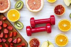 Asortyment różnorodne kolorowe owoc z dumbbells, odgórny widok koncepcja kulowego fitness pilates złagodzenie fizycznej Zdjęcie Stock