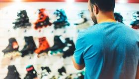 Asortyment rolkowe łyżwy odizolowywać w sklepu sklepie, osoby wybierać i zakupu koloru wrotkach na backgraund słońcu, migoczą, zd obraz stock