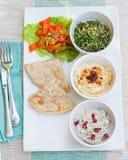 Asortyment upady: hummus, chickpea upad, tabbouleh sałatka, baby ganoush i mieszkanie chleb, pita Obrazy Stock