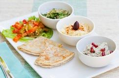 Asortyment upady: hummus, chickpea upad, tabbouleh sałatka, baby ganoush i mieszkanie chleb, pita na talerzu Obrazy Stock