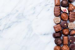 Asortyment ?wietni czekoladowi cukierki, biel, zmrok i dojna czekolada, Marmurowy t?o kosmos kopii Odg?rny widok obrazy royalty free
