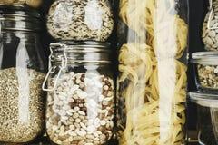 Asortyment zbożowi produkty i makaron w szklanych składowych zbiornikach na drewnianym stole Zdrowy kucharstwo, czysty łasowanie, obraz royalty free
