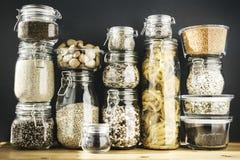 Asortyment zbo?owi produkty i makaron w szklanych sk?adowych zbiornikach na drewnianym stole Zdrowy kucharstwo, czysty ?asowanie, fotografia royalty free