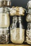 Asortyment zbo?owi produkty i makaron w szklanych sk?adowych zbiornikach na drewnianym stole Zdrowy kucharstwo, czysty ?asowanie, obraz royalty free