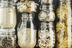 Asortyment zbo?owi produkty i makaron w szklanych sk?adowych zbiornikach na drewnianym stole Zdrowy kucharstwo, czysty ?asowanie, obrazy royalty free