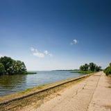 Aspalt drogowa pobliska rzeka pod chmurnym niebem Zdjęcia Royalty Free