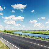 Aspalt road near river under clouds Stock Image