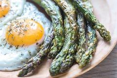 Asparago arrostito con le uova fritte Fotografia Stock