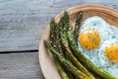 Asparago arrostito con le uova fritte sul piatto Fotografie Stock Libere da Diritti