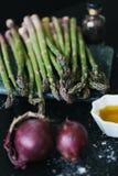 Asparago con la cipolla e l'olio d'oliva Fotografie Stock
