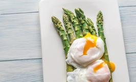 Asparago cotto a vapore con gli uova affogate sul piatto Fotografia Stock