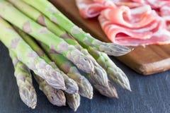 Asparago e bacon verdi sul fondo scuro dell'ardesia, ingredienti Immagine Stock Libera da Diritti