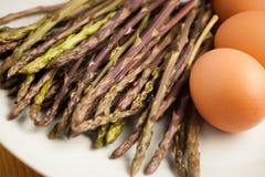 Asparago selvaggio fresco su un piatto con le uova pronte ad essere cucinato Fotografia Stock