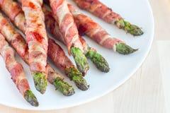 Asparago verde avvolto con bacon sul piatto bianco, orizzontale Immagine Stock Libera da Diritti