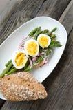 Asparago verde con l'uovo affogato su un piatto Fotografia Stock Libera da Diritti