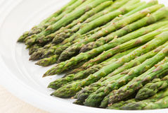 Asparagus. Organic roasted asparagus sprinkled with salt, pepper, garlic and other herbs served in a white plate. Shot in natural light. Selective focus with Royalty Free Stock Photo