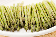 Asparagus. Roasted asparagus sprinkled with salt, pepper, garlic and herbs. Served on a white plate. Shot in natural light. Shallow DOF with selective focus Royalty Free Stock Images