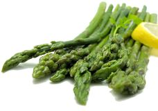 Asparagus. Plate of steamed asparagus with lemon and parsley on white Stock Photos