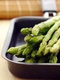 Asparagus. In black pan on kitchen table Royalty Free Stock Photography