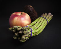 Asparagus, apple and avocado on black background. Stock Image