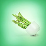 Asparagus arrange in a white cup  on natural green background Royalty Free Stock Image