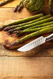 Asparagus. and an artichoke on a cutting board with a knife, sliced. on a wooden background. Culinary background. Diet. Delicious.  stock photos