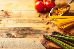 Asparagus, and the artichoke and sprig of tomatoes and sweet red pepper and Italian spaghetti on a cutting board with a knife,. Sliced. on wooden background royalty free stock photography