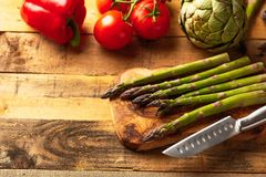 Asparagus, and an artichoke, a sprig of tomatoes and sweet red peppers on a cutting board with a knife, sliced. on a wooden.  stock image