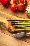 Asparagus, and an artichoke, a sprig of tomatoes and sweet red peppers on a cutting board with a knife, sliced. on a wooden. Background. a culinary background stock image
