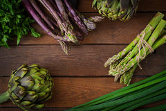 Asparagus and artichokes with herbs on a wooden background. Stock Image