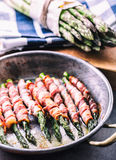 Asparagus. Asparagus and roll bacon. Grilled asparagus with rolled bacon and fried egg. Fried old pan full of rolled bacon with Stock Image