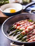 Asparagus. Asparagus and roll bacon. Grilled asparagus with rolled bacon and fried egg. Fried old pan full of rolled bacon with Stock Photo