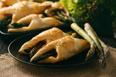 Asparagus baked in puff pastry with ham and cheese. stock photography