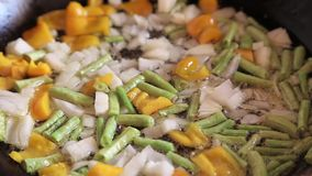 Asparagus beans in a frying pan. With onions and carrots are fried, a useful summer dish stock video footage