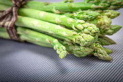 Asparagus bind with brown ribbon on blue grey background Royalty Free Stock Images