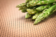Asparagus bind with brown ribbon on brown wickerwork background Royalty Free Stock Photography
