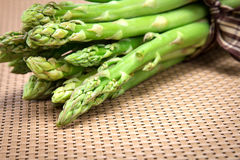 Asparagus bind with brown ribbon on brown wickerwork background Stock Photos