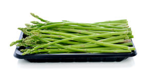 Asparagus in black plastic tray. On a white background stock image