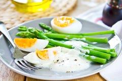 Asparagus with boiled eggs Stock Photos