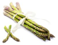 Asparagus. Bunch of raw asparagus tied with a creamy knot and two cut pieces isolated on white background Royalty Free Stock Image