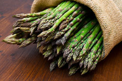 Asparagus in burlap sack on wood Stock Image
